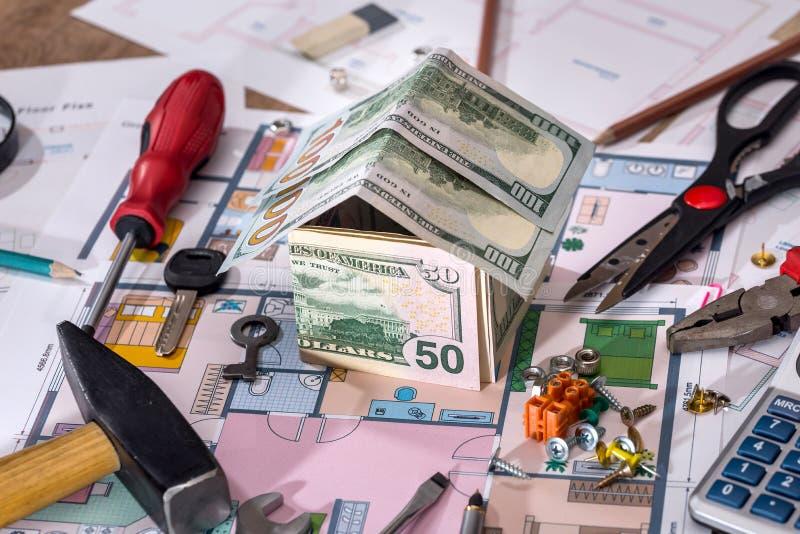 Hus för arkitektoniskt plan med pengar, blyertspenna, räknemaskin arkivfoton