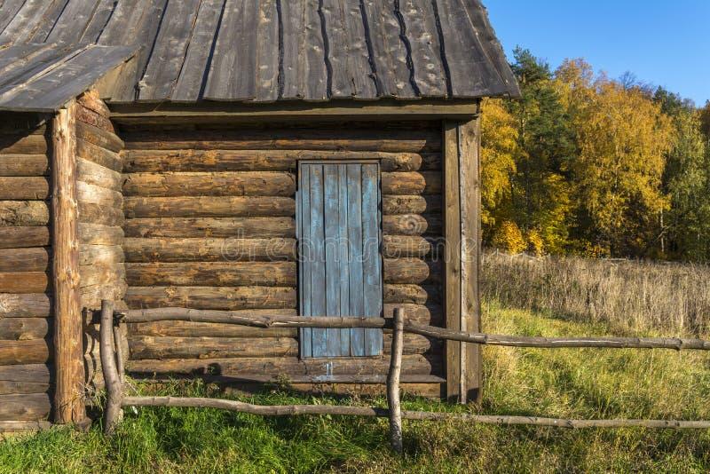 Hus för gammalt land som göras av journaler Trädörr till gården Ett staket som göras av trästrålar royaltyfri foto