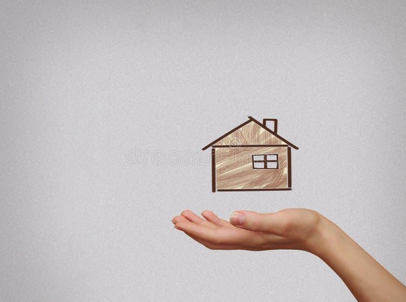 Hus för illustration för kvinnahand hållande på grå bakgrund Insura royaltyfria bilder