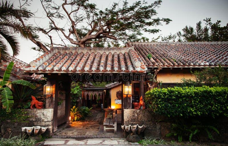 Hus för japanOkinawa stil med tegelplattataket i trädgård royaltyfri foto