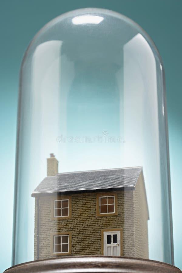 Hus för liten modell under den glass räkningen royaltyfria foton