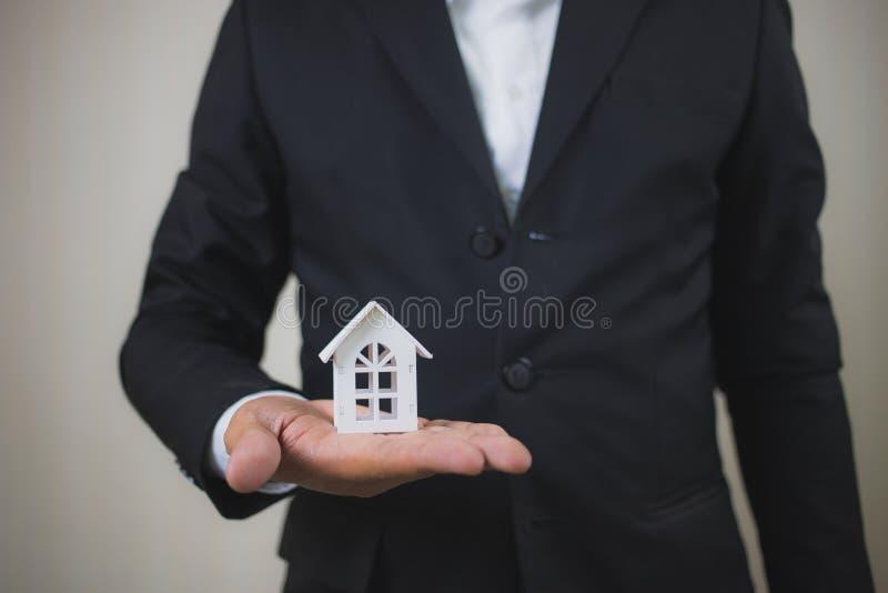 Hus för modell för affärsmanhandinnehav vitt Det egenskapsinvesteringen och huset intecknar det finansiella begreppet, hem skydda royaltyfria foton