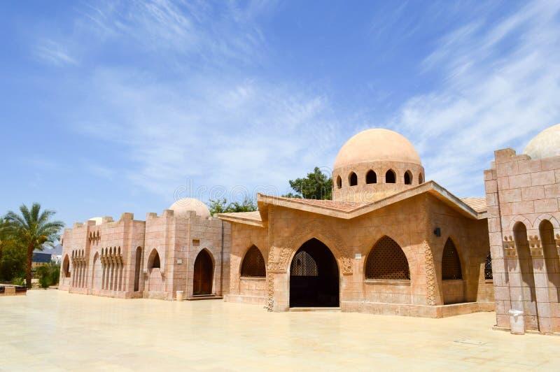 Hus för muselman för liten härlig proper gammal forntida stenlera arabiska islamiska med runda kupoler i öknen med palmträd i en  arkivfoto