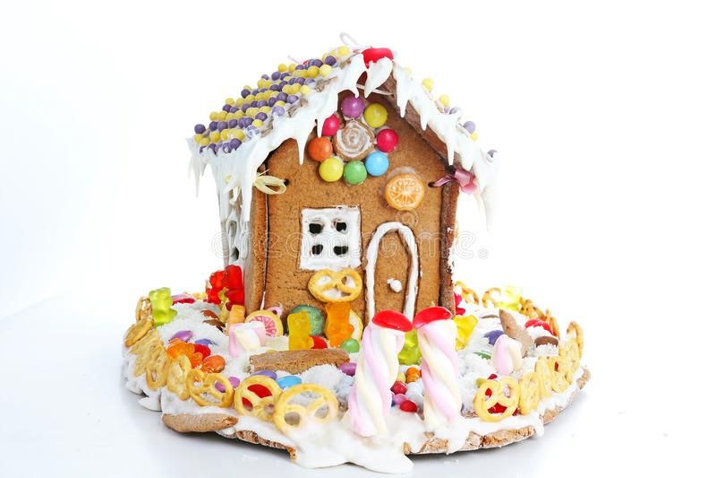 Hus för pepparkakagodissocker Felik svanscandyhouse som täckas med det hemlagade pepparkakahuset för snö och för färgrika godisar royaltyfri foto