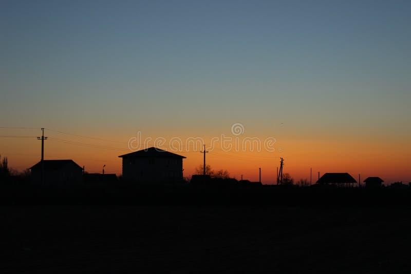 Hus för soluppgång bakifrån på havet arkivbilder