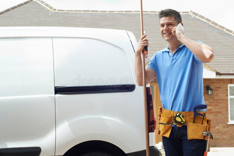 Hus för yttersida för rörmokareWith Van Making Call On Mobile telefon royaltyfria foton