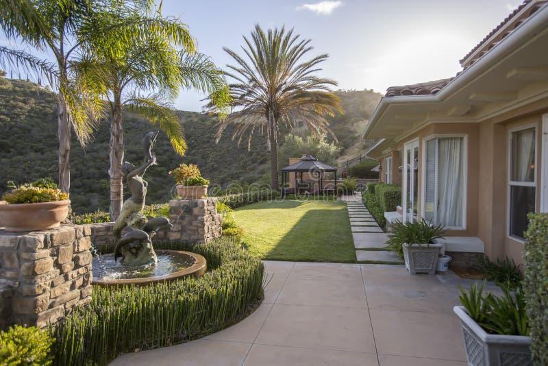 Hus-, gräsmatta- och vattensärdrag i det San Diego hemmet royaltyfri foto