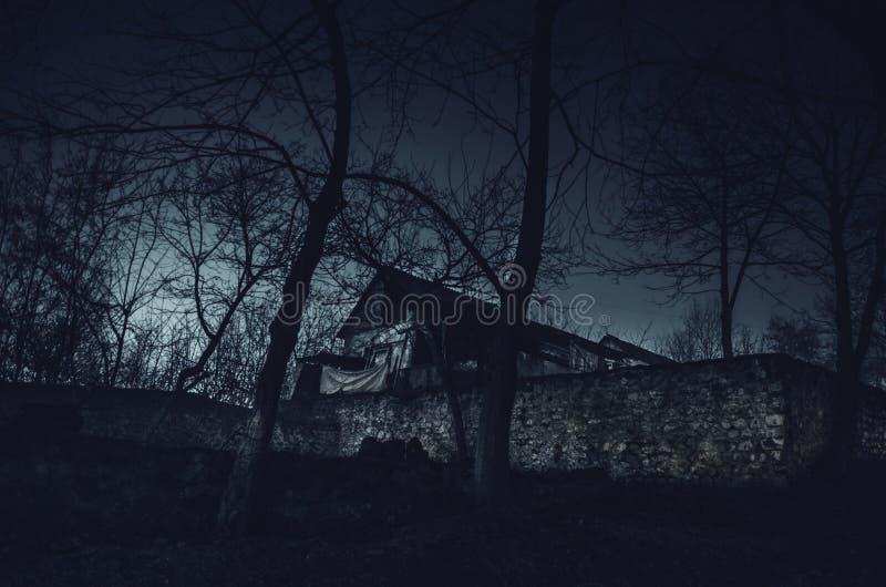 Hus i dimma på natten i trädgården, landskap av spökehuset i den mörka skogen arkivfoton