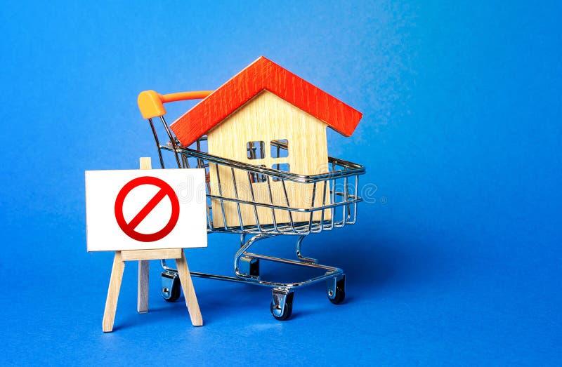Hus i en shoppingvagn och ål med rött förbudsskylt NO Otillgänglighet, bostadsbrist, underskott Beslag, frysning royaltyfria bilder