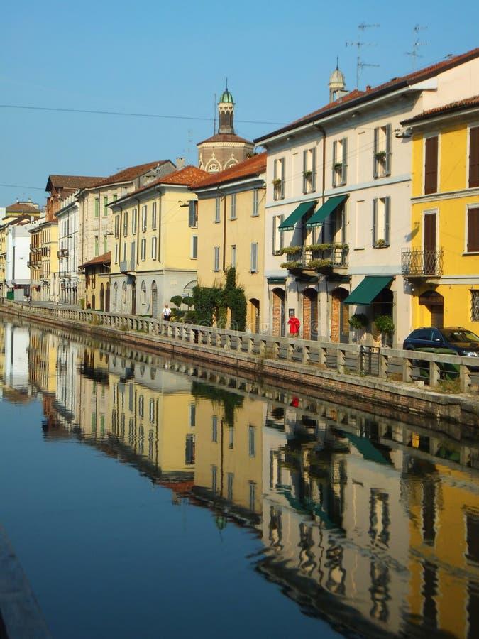 Hus längs Naviglioen som är stor i Milan på en ljus sommarmorgon, reflekterad i det lugna vattnet av kanalen royaltyfria bilder
