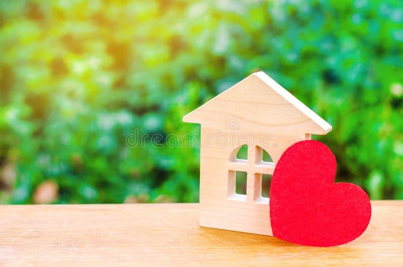 Hus med en röd hjärta Hus av vänner Som man har råd med hus för unga familjer Hus för dag för valentin` s fotografering för bildbyråer