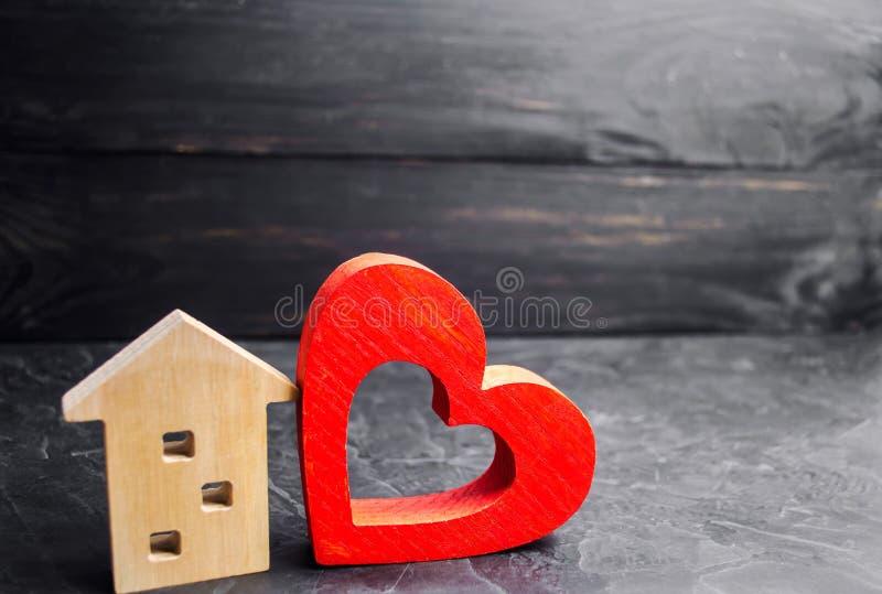 Hus med en röd hjärta Hus av vänner Som man har råd med hus för unga familjer Hus för dag för valentin` s royaltyfri foto