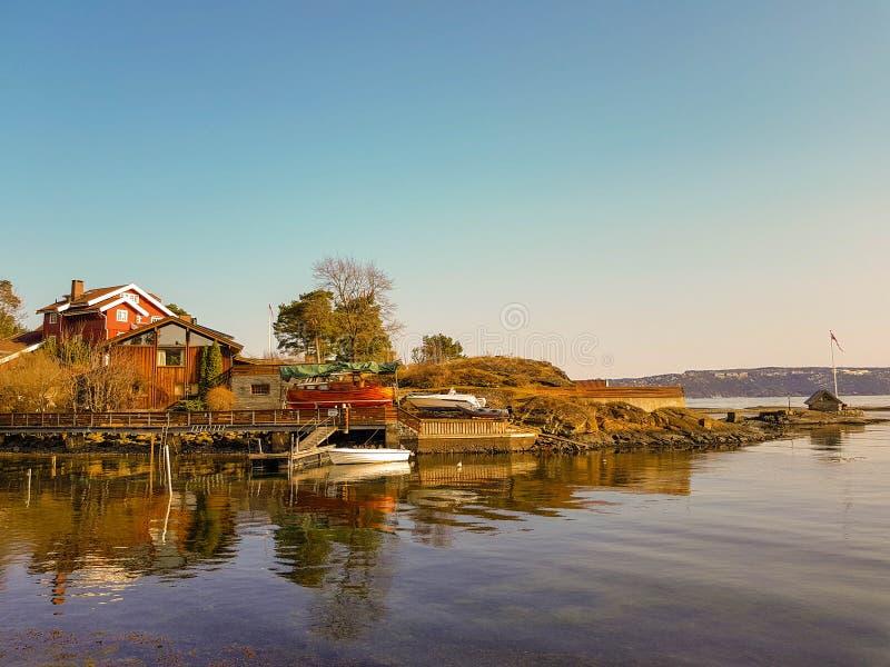 Hus med ett fartyg på banken av en fjord i Oslo fotografering för bildbyråer