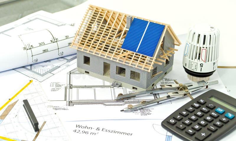 Hus med ett konstruktionsplan och en solpanelplanläggning royaltyfri foto