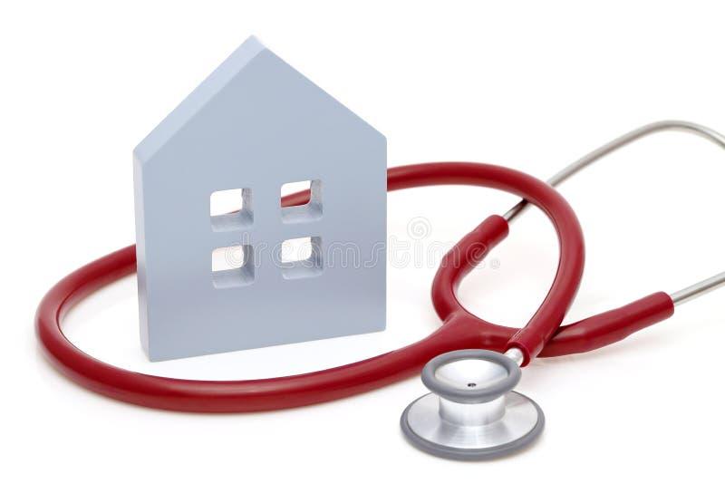 Hus med stetoskopet som isoleras p? vit bakgrund Modellera huset med stetoskopet fotografering för bildbyråer