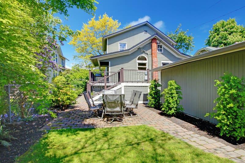 Hus med trädgårdsammanträdeområde och garageväggen. fotografering för bildbyråer