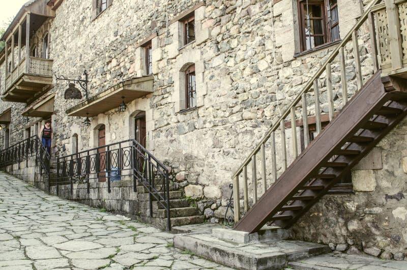 Hus med väggar av den grova stenen, dekorativa skyddsgallrar för smidesjärn, träbalkonger i museet Tufenkian gamla Dilijan royaltyfri bild