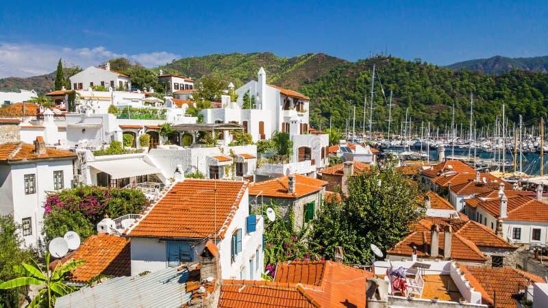Hus med vita väggar och orange fjärdedelar för belade med tegel tak av nollan royaltyfria foton