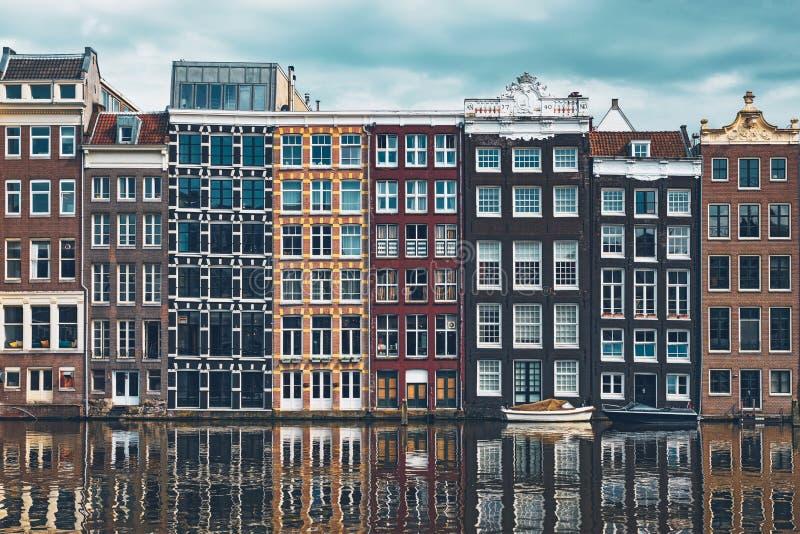 hus och fartyg på den Amsterdam kanalen Damrak med reflexion amuletter royaltyfri fotografi