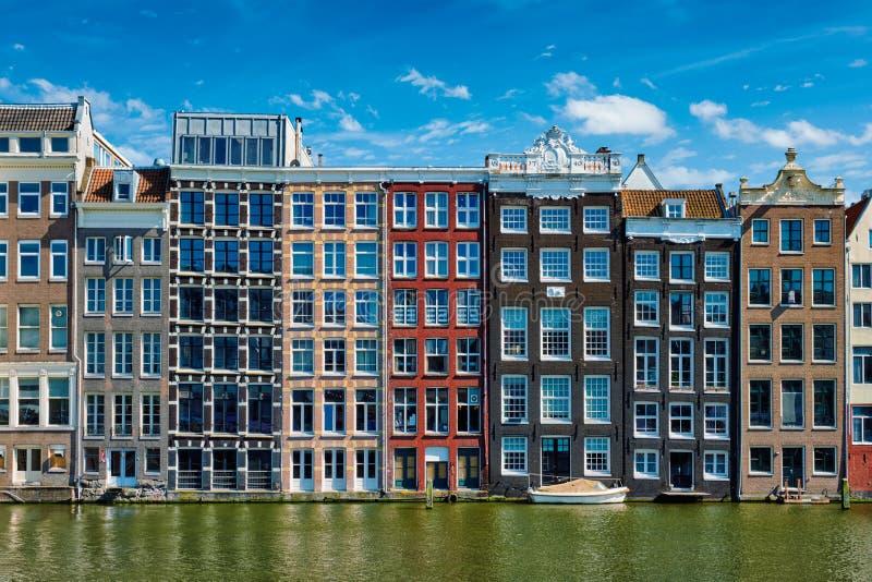 hus och fartyg på den Amsterdam kanalen Damrak med reflexion amuletter arkivfoto