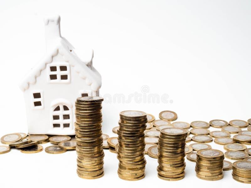 Hus- och myntbunten på vit bakgrund intecknar sparande begrepp arkivfoton