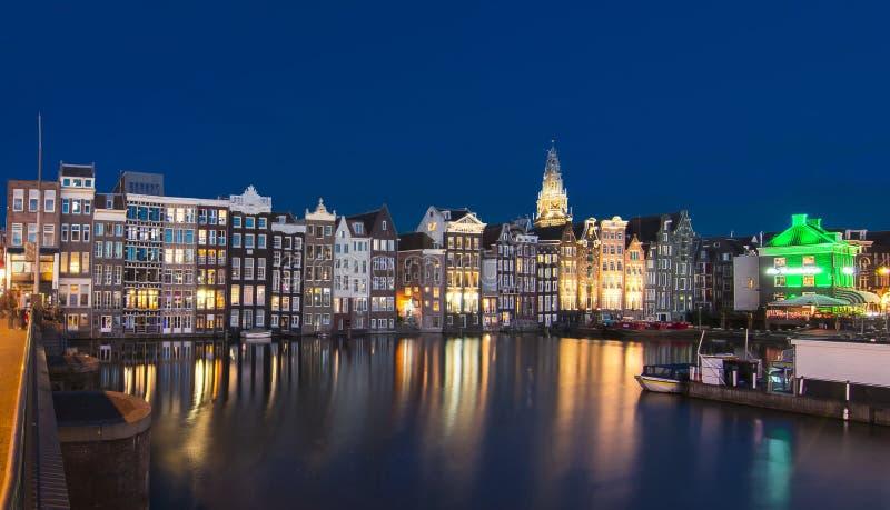 Hus på den Damrak kanalen på natten, Amsterdam, Nederländerna royaltyfria bilder