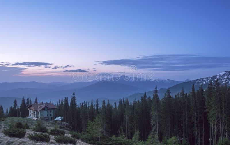 Hus på en bergkulle på soluppgång Förlägga i barack i en skog med sikt på en bergskedja arkivbild