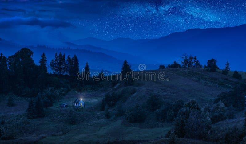Hus på en bergkulle under den stjärnklara himlen royaltyfri bild