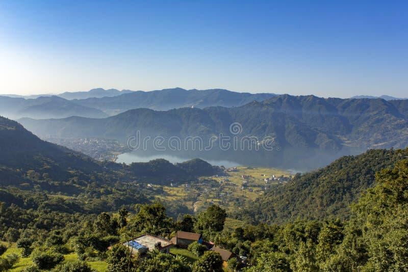 Hus på en kulle, mot bakgrunden av staden av Pokhara i en dimmig morgondal för berg med Phewa sjön under en frikänd arkivbilder