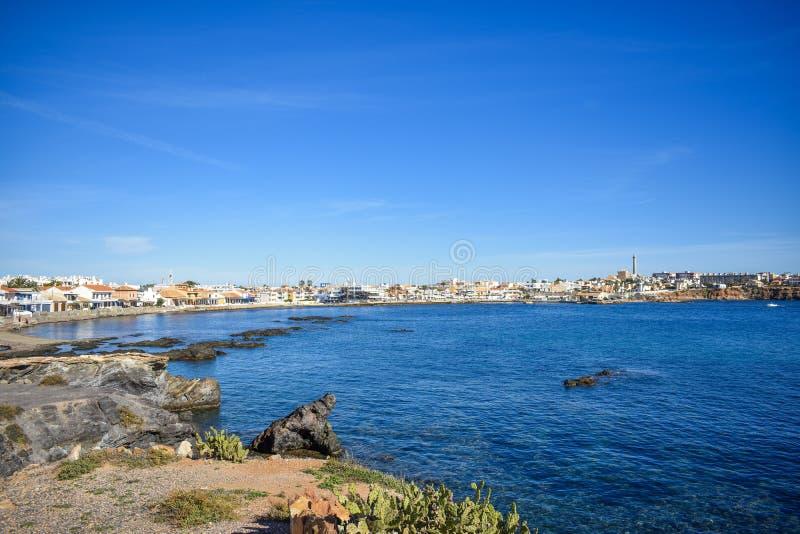 Hus på ett stenigt beachfront på Cabo de Palos, Spanien royaltyfri bild