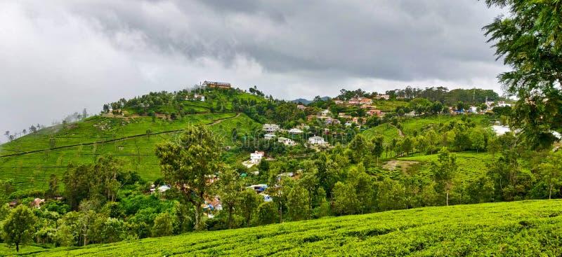 Hus på kullarna av Coonoor under de regniga molnen av monsun arkivbild