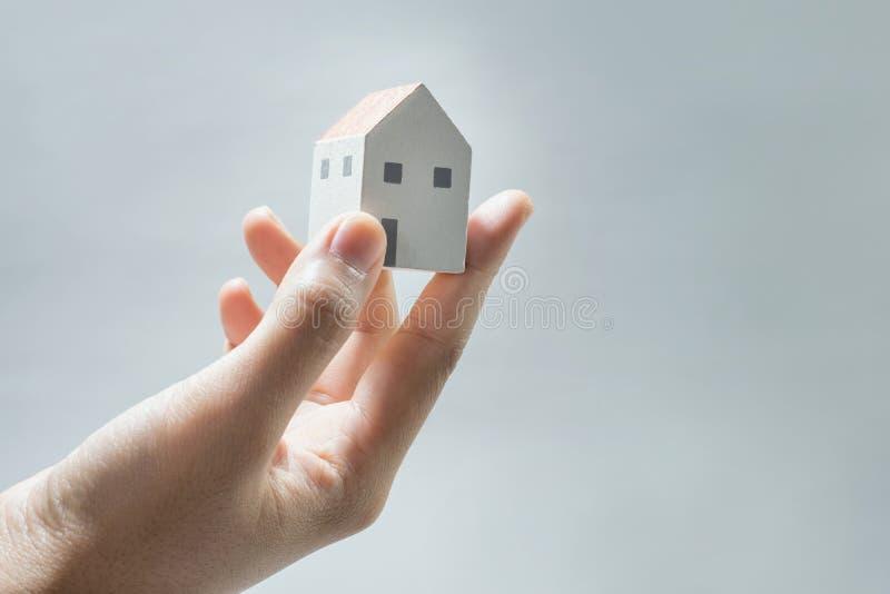 Hus på mänskliga händer Besparingpengar, byggnadskonstruktion, arkitektur arkivfoto