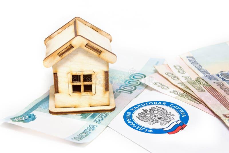 Hus, pengar och ett brev från skattkontoret royaltyfri foto