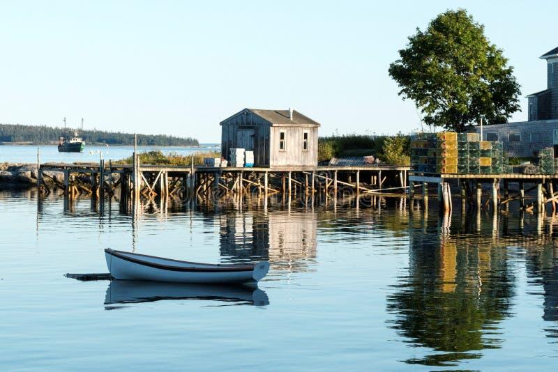 Hus, skeppsdocka, radfartyg och hummerfällor som reflekterar i vattnet arkivbild