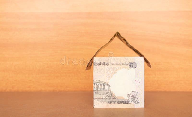 Hus som göras från den indiska valutan med kopieringsutrymme, begrepp av konstruering av huset med pengar royaltyfri foto