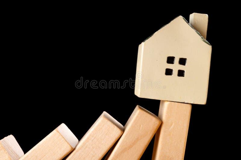 Hus som ner faller från ett dominobrickagrundbegrepp av fastighetsinvesteringen royaltyfri fotografi