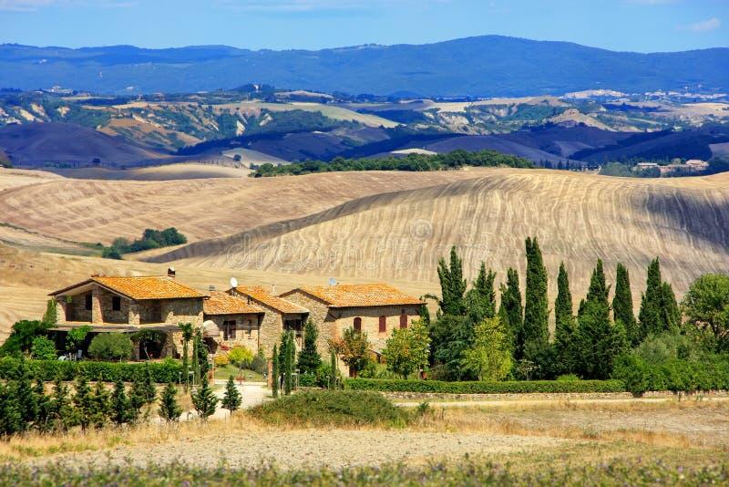 Hus som omges av fält i Val D ` Orcia, Tuscany, Italien arkivfoton