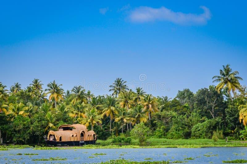Husbåt i avkrokar av Kerala mot tjock grönska och ett b arkivfoto