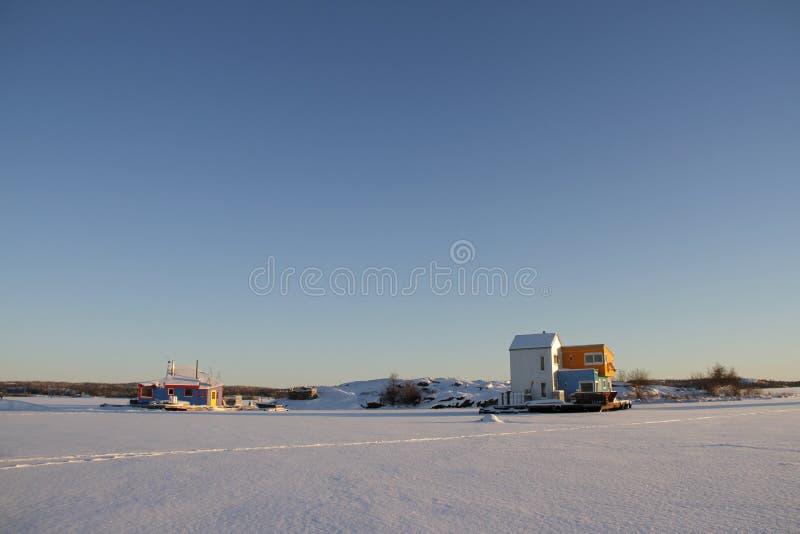 Husbåtar nära en ö på Yellowknife skäller i stora slav- Lake arkivfoton