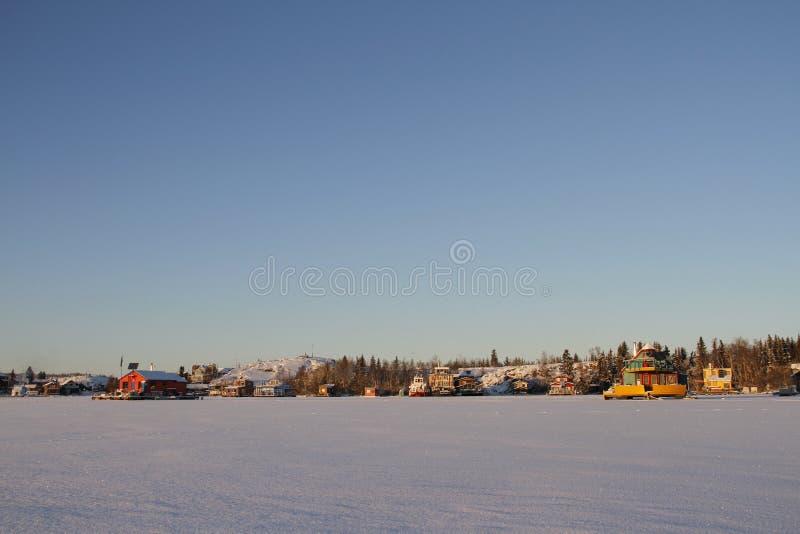 Husbåtar på Yellowknife skäller i stora slav- Lake på solnedgången arkivfoto