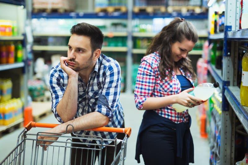 Husband bored while shopaholic woman enjoys stock image