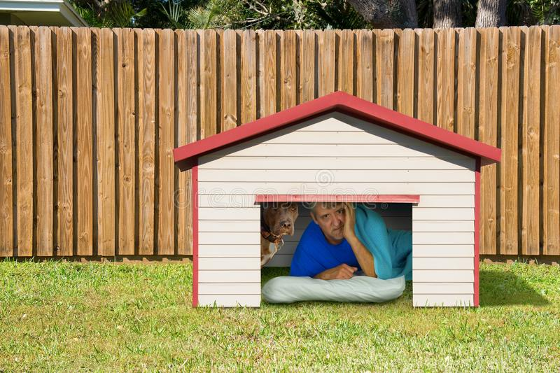 Husband or boyfriend man sleeping in the doghouse because of domestic problems royalty free stock image