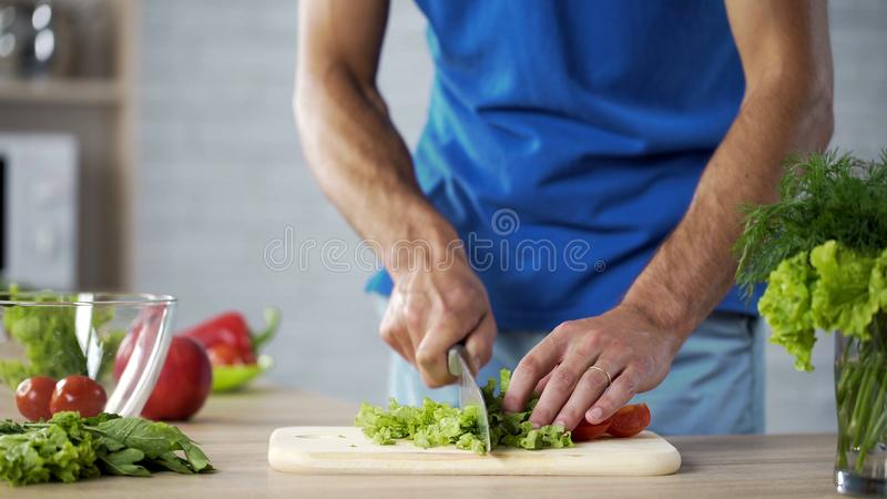 Husband cutting fresh salad on board for healthy family lunch, cooking help stock photo