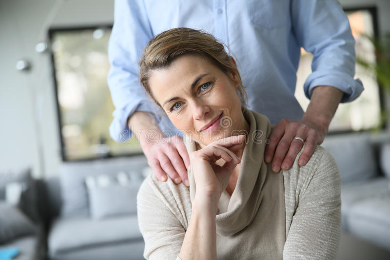 Husband giving relaxing shoulder massage to his wife royalty free stock image