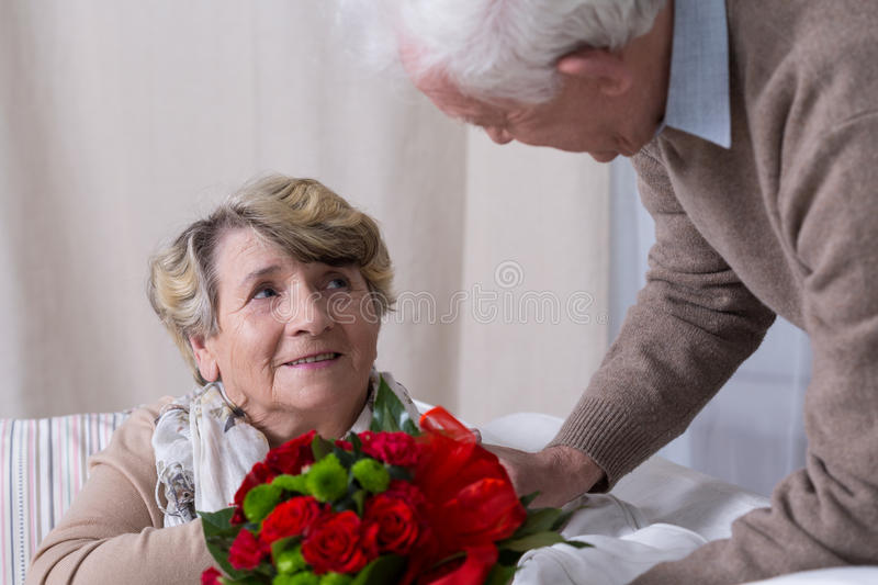 Husband giving wife anniversary gift royalty free stock images