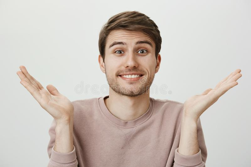 Husband has no idea. Indoor portrait of beautiful young man with bristle shrugging and raising palms, smiling awkwardly royalty free stock photos