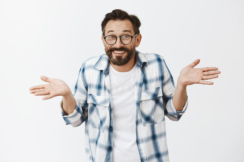 Husband hid wifes phone, making innocent expression as if he unaware and clueless. Charming happy and carefree man with. Beard and wrinkles in glasses, shoulder stock photo