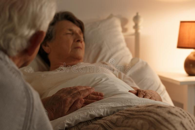 Husband holding dying wife`s hand. Husband holding hand of his ill dying at home wife royalty free stock photo