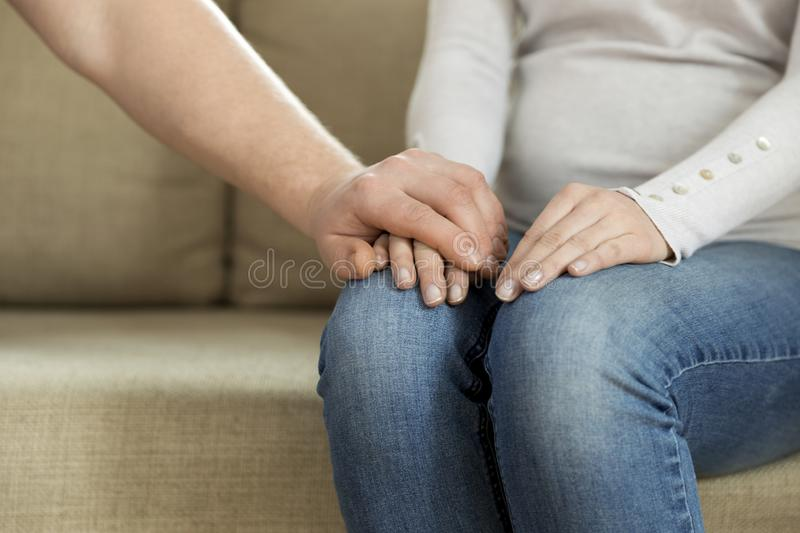 Husband holding hand of his wife, giving emotional support. Mental benefits of marriage. Conversation and friendship royalty free stock photos