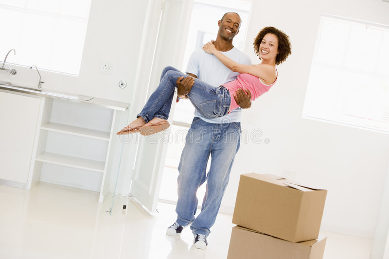 Husband holding wife in new home smiling stock images